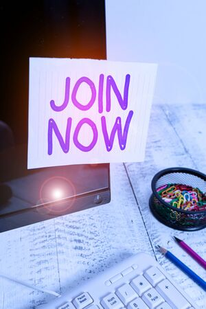Conceptual hand writing showing Join Now. Concept meaning An invite to a demonstrating or a friend to become a member of the group Note paper taped to black screen near keyboard stationary