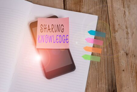 Word writing text Sharing Knowledge. Business photo showcasing knowledge is exchanged among showing or organizations Note book four arrow banners smartphone sticky note old wooden background Stock Photo