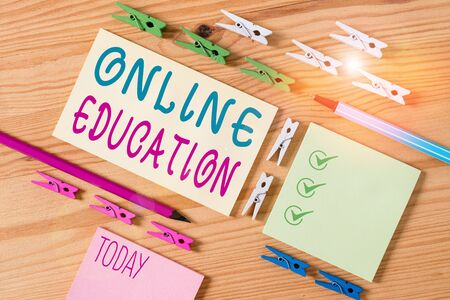 Conceptual hand writing showing Online Education. Concept meaning kind of learning that takes place via the Internet Colored crumpled papers wooden floor background clothespin