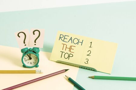 Text sign showing Reach The Top. Business photo text Get Ahead Succeed Prosper Thrive for the Win Victory Mini size alarm clock beside stationary placed tilted on pastel backdrop