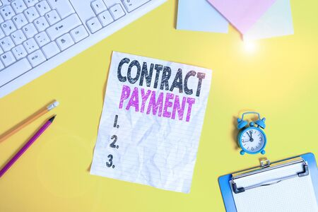 Text sign showing Contract Payment. Business photo text payments made by payer to the payee as per agreement terms Copy space on notebook above yellow background with keyboard on table