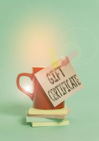 Writing note showing Gift Certificate. Business concept for certificate entitling the recipient to receive goods Cup colored sticky note banners stacked pads lying pastel background