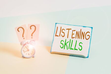 Conceptual hand writing showing Listening Skills. Concept meaning ability to understand information provided by the speaker Alarm clock beside a Paper sheet placed on pastel backdrop Stock fotó