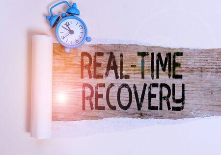Text sign showing Real Time Recovery. Business photo showcasing maximum time period in which recent data can recover Alarm clock and torn cardboard placed above a wooden classic table backdrop Stock fotó