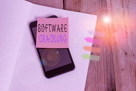 Word writing text Software Cracking. Business photo showcasing modification of software to remove or disable features Note book four arrow banners smartphone sticky note old wooden background