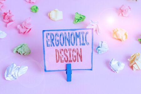 Word writing text Ergonomic Design. Business photo showcasing fitting or designing a workplace to the user s is needs Colored crumpled papers empty reminder pink floor background clothespin