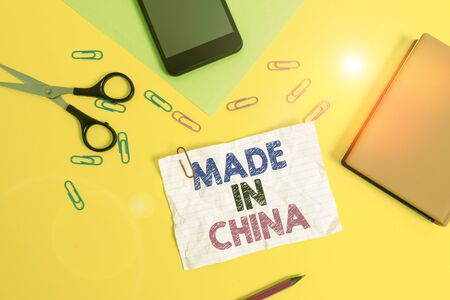 Text sign showing Made In China. Business photo text Wholesale Industry Marketplace Global Trade Asian Commerce Paper sheets pencil clips smartphone scissors notebook colored background