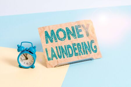 Text sign showing Money Laundering. Business photo text concealment of the origins of illegally obtained money Mini size alarm clock beside a Paper sheet placed tilted on pastel backdrop Zdjęcie Seryjne