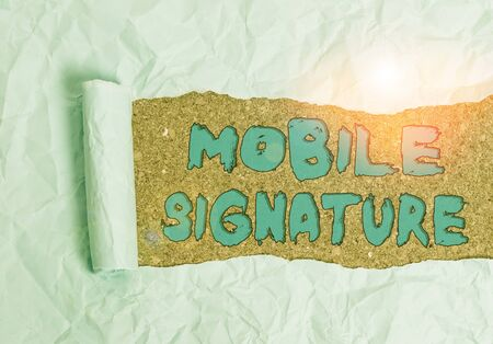Word writing text Mobile Signature. Business photo showcasing digital signature generated either on a mobile phone Cardboard which is torn in the middle placed above a wooden classic table Reklamní fotografie
