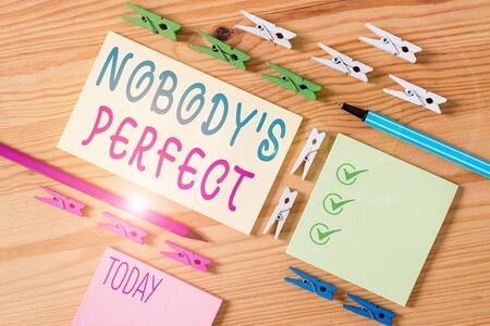 Conceptual hand writing showing Nobody S Is Perfect. Concept meaning used to say that everyone makes mistakes or fault Colored crumpled papers wooden floor background clothespin Zdjęcie Seryjne