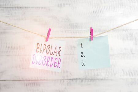 Text sign showing Bipolar Disorder. Business photo showcasing mental illness that brings severe high and low moods Clothesline clothespin rectangle shaped paper reminder white wood desk