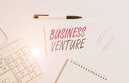 Text sign showing Business Venture. Business photo showcasing new business that is formed with a plan and expect gain White pc keyboard with empty note paper and pencil above white background Imagens