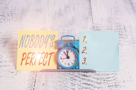 Conceptual hand writing showing Nobody S Is Perfect. Concept meaning used to say that everyone makes mistakes or fault Mini blue clock standing above buffer wire between two paper Zdjęcie Seryjne