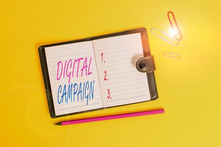 Conceptual hand writing showing Digital Campaign. Concept meaning effort put forward by a company to drive engagement Dark leather locked diary striped sheets marker colored background
