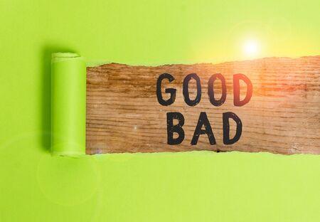 Wort schreiben Text gut schlecht. Geschäftsfoto, das ein gutes oder schlechtes Ergebnis zu zeigen scheint Lebensentscheidungen Karton, der in der Mitte über einem klassischen Holztisch gerissen ist Standard-Bild