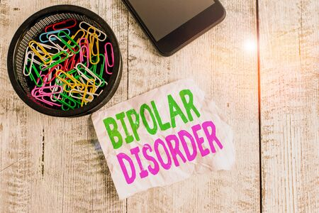 Writing note showing Bipolar Disorder. Business concept for mental illness that brings severe high and low moods Wrinkle paper and cardboard placed above wooden background