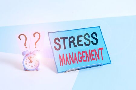 Writing note showing Stress Management. Business concept for learning ways of behaving and thinking that reduce stress Alarm clock beside a Paper sheet placed on pastel backdrop