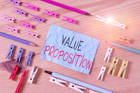 Conceptual hand writing showing Value Proposition. Concept meaning make a company or product attractive to customers Colored crumpled papers wooden floor background clothespin