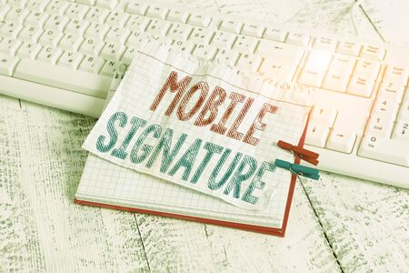 Text sign showing Mobile Signature. Business photo text digital signature generated either on a mobile phone notebook paper reminder clothespin pinned sheet white keyboard light wooden Reklamní fotografie