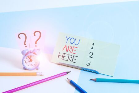 Text sign showing You Are Here. Business photo text This is your location reference point global positioning system Mini size alarm clock beside stationary placed tilted on pastel backdrop