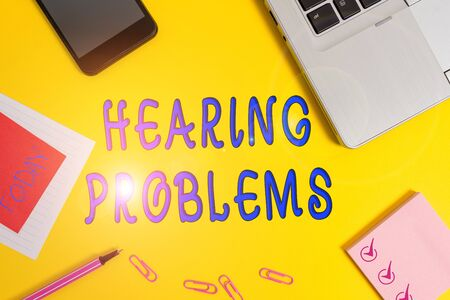 Text sign showing Hearing Problems. Business photo text partial or total inability to hear Hearing impairment Laptop smartphone notepad marker paper sheet note clips colored background