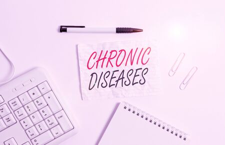 Text sign showing Chronic Diseases. Business photo showcasing A disease or condition that lasts for longer time White pc keyboard with empty note paper and pencil above white background