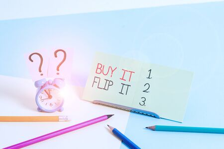 Text sign showing Buy It Flip It. Business photo text Buy something fix them up then sell them for more profit Mini size alarm clock beside stationary placed tilted on pastel backdrop Stock fotó