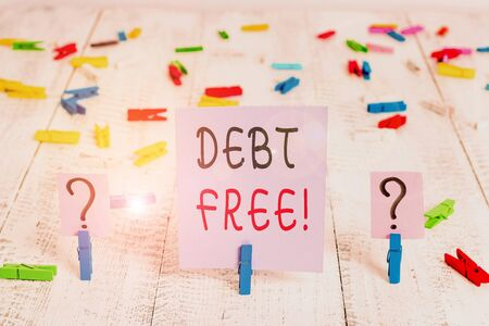 Writing note showing Debt Free. Business concept for does not owning any money to any individual or companies Crumbling sheet with paper clips placed on the wooden table