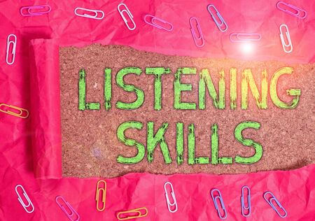 Conceptual hand writing showing Listening Skills. Concept meaning ability to understand information provided by the speaker Paper clip and torn cardboard on wood classic table backdrop