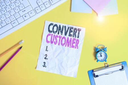 Text sign showing Convert Customer. Business photo text the percentage of visitors who take the desired action Copy space on notebook above yellow background with keyboard on table