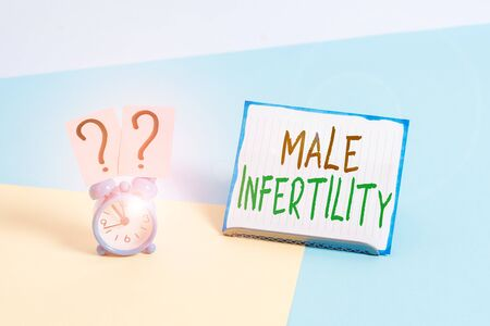 Conceptual hand writing showing Male Infertility. Concept meaning the inability to cause pregnancy in a fertile Alarm clock beside a Paper sheet placed on pastel backdrop
