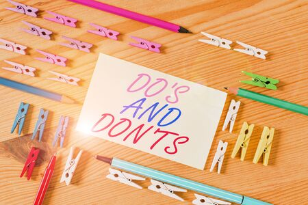 Handwriting text Do S And Don Ts. Conceptual photo Technologically complication of making a decision Colored clothespin papers empty reminder wooden floor background office