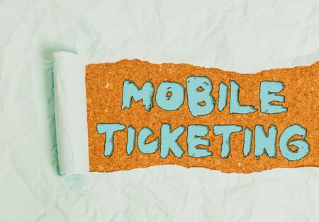 Word writing text Mobile Ticketing. Business photo showcasing tickets arrive as a text message with a special barcode Cardboard which is torn in the middle placed above a wooden classic table Standard-Bild