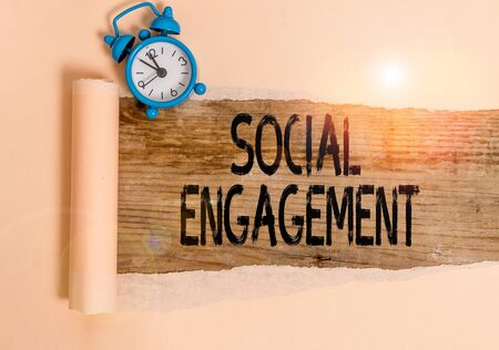 Text sign showing Social Engagement. Business photo showcasing one s is degree of participation in a community or society Alarm clock and torn cardboard placed above a wooden classic table backdrop