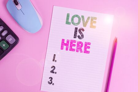Text sign showing Love Is Here. Business photo text Roanalysistic feeling Lovely emotion Positive Expression Care Joy Electronic calculator wire mouse striped sheet pencil colored background