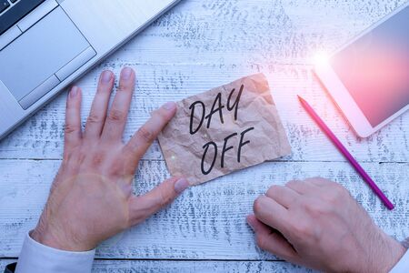 Writing note showing Day Off. Business concept for when you do not go to work even though it is usually a working day Hand hold note paper near writing equipment and smartphone Archivio Fotografico