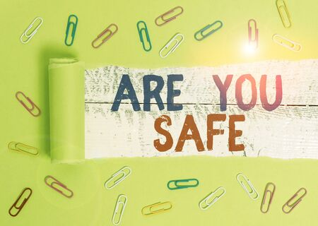 Text sign showing Are You Safe. Business photo text Free from danger Not anticipating any Harm Hurt physically Paper clip and torn cardboard placed above a wooden classic table backdrop Stock Photo