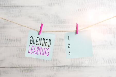 Text sign showing Blended Learning. Business photo showcasing combines traditional classroom lessons with online teaching Clothesline clothespin rectangle shaped paper reminder white wood desk