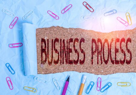 Conceptual hand writing showing Business Process. Concept meaning implemented to accomplish a target organizational goal Stationary and torn cardboard on a wooden classic table backdrop Stock Photo