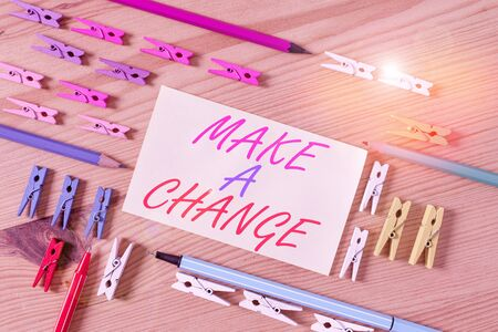 Handwriting text Make A Change. Conceptual photo Create a Difference Alteration Have an Effect Metamorphose Colored clothespin papers empty reminder wooden floor background office