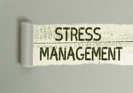 Writing note showing Stress Management. Business concept for learning ways of behaving and thinking that reduce stress Cardboard which is torn placed above a wooden classic table