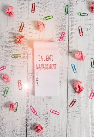 Writing note showing Talent Management. Business concept for anticipation of required huanalysis capital for an organization Stripped ruled notepad clips paper balls wooden background Foto de archivo