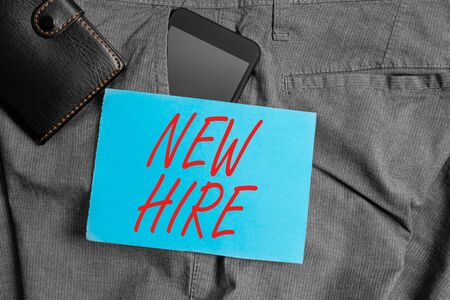 Conceptual hand writing showing New Hire. Concept meaning someone who has not previously been employed by the organization Smartphone device inside trousers front pocket with wallet
