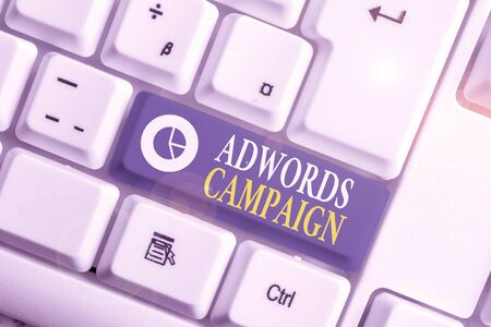 Word writing text Adwords Campaign. Business photo showcasing strategy for targeting right visitors with right keywords White pc keyboard with empty note paper above white background key copy space
