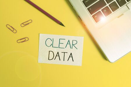 Word writing text Clear Data. Business photo showcasing act of removing unwanted data or information in a storage disk Trendy metallic laptop clips pencil squared paper sheet colored background