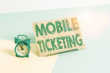 Textschild mit Mobile Ticketing. Geschäftsfoto-Texttickets kommen als Textnachricht mit einem speziellen Barcode-Wecker in Mini-Größe neben einem Papierblatt an, das geneigt auf einem pastellfarbenen Hintergrund platziert ist