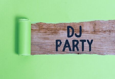 Word writing text Dj Party. Business photo showcasing demonstrating who introduces and plays recorded popular music on radio Cardboard which is torn in the middle placed above a wooden classic table