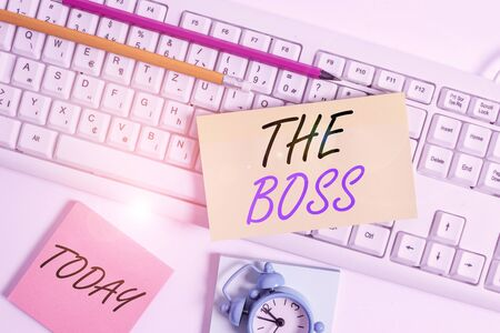 Text sign showing The Boss. Business photo showcasing a demonstrating who exercises control or authority in the organization Flat lay above empty note paper on the pc keyboard pencils and clock
