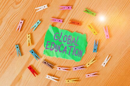 Word writing text Global Education. Business photo showcasing ideas taught to enhance one s is perception of the world Colored clothespin papers empty reminder wooden floor background office
