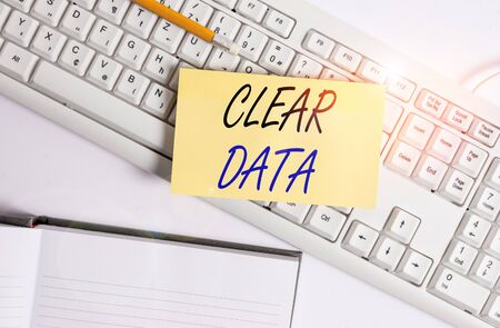 Word writing text Clear Data. Business photo showcasing act of removing unwanted data or information in a storage disk White pc keyboard with empty note paper and paper clips above white background